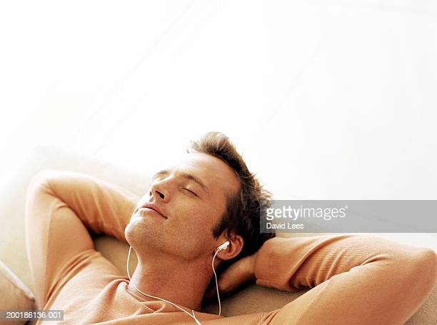 man relaxing with hands behind head, wearing headphones, eyes closed - zurücklehnen stock-fotos und bilder