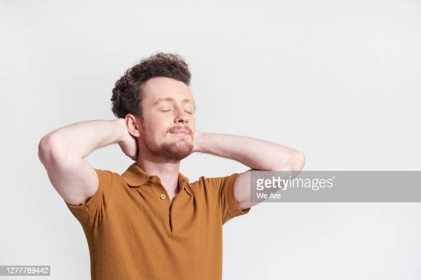 man relaxing with hands behind his head - tranquility stock pictures, royalty-free photos & images