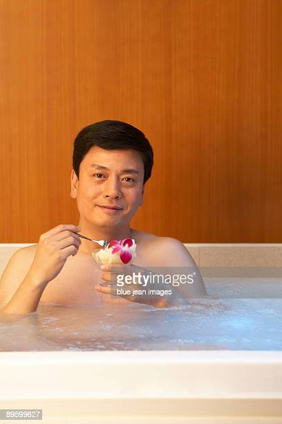 Man relaxing with some fruit in a hot tub