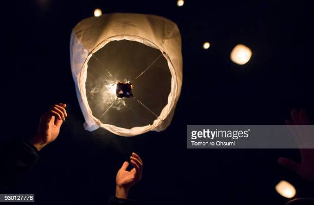 A man releases a paper lantern into the air during the Tsunan Sky Lantern event on March 10 2018 in Tsunan Japan About 2000 lanterns were released at...