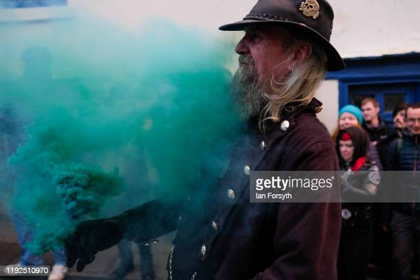 A man releases green smoke as participants walk through the streets during the annual Whitby Krampus parade on December 07 2019 in Whitby England The...