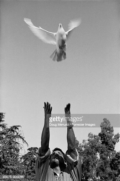 Man Releasing Dove