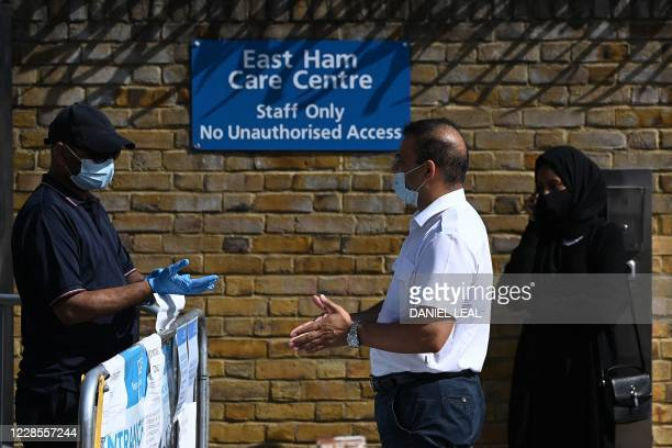 A man remonstrates with a worker about the lack of COVID19 testing appointments outside the entrance to a novel coronavirus walkin testing centre in...