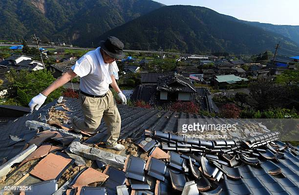 A man remove roof tiles of his damaged house on April 20 2016 in Minamiaso Kumamoto Japan A total of 42 people have died and roughly 1100 have been...