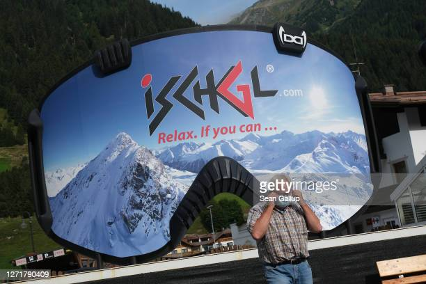 A man removes a protective face mask after photographing himself in front of an advertisement in the shape of ski goggles for the Ischgl ski resort...