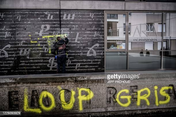 Man removes an outside wall of the National Armenian Memorial Centre in Decines-Charpieu, near Lyon, on November 1, 2020 where pro-Turkish yellow...