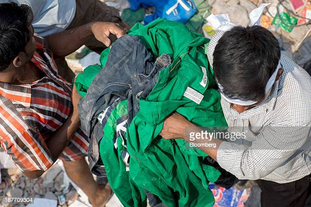 A man removes clothing bearing a label that reads 'Joe Fresh' from around the devastated area of the collapsed Rana Plaza building in Dhaka...