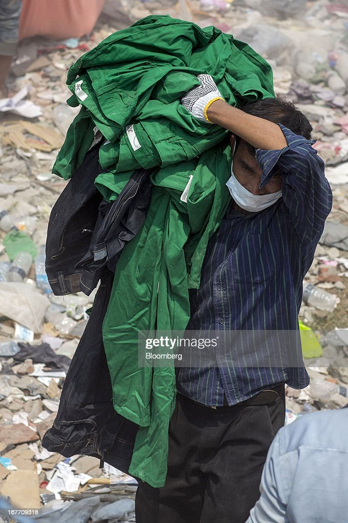 A man removes clothing bearing a label that reads 'Joe Fresh' from around the devastated area of the collapsed Rana Plaza building in Dhaka, Bangladesh, on Friday, April 26, 2013. The day after a Bangladesh building collapsed, killing more than 290 people, disagreement emerged over whether the owner obtained appropriate construction permits, adding to concerns over worker safety in the country's garment industry. Photographer: Jeff Holt/Bloomberg via Getty Images