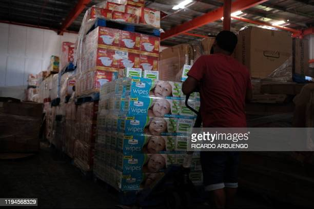 A man removes diapers and baby wipes from a warehouse filled with supplies believed to have been from when Hurricane Maria struck the island in 2017...