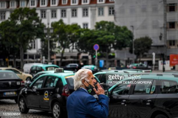 Man removes his face mask to smoke a cigarette in downtown Lisbon on October 28, 2020. - The Portuguese support the wearing of the compulsory mask...