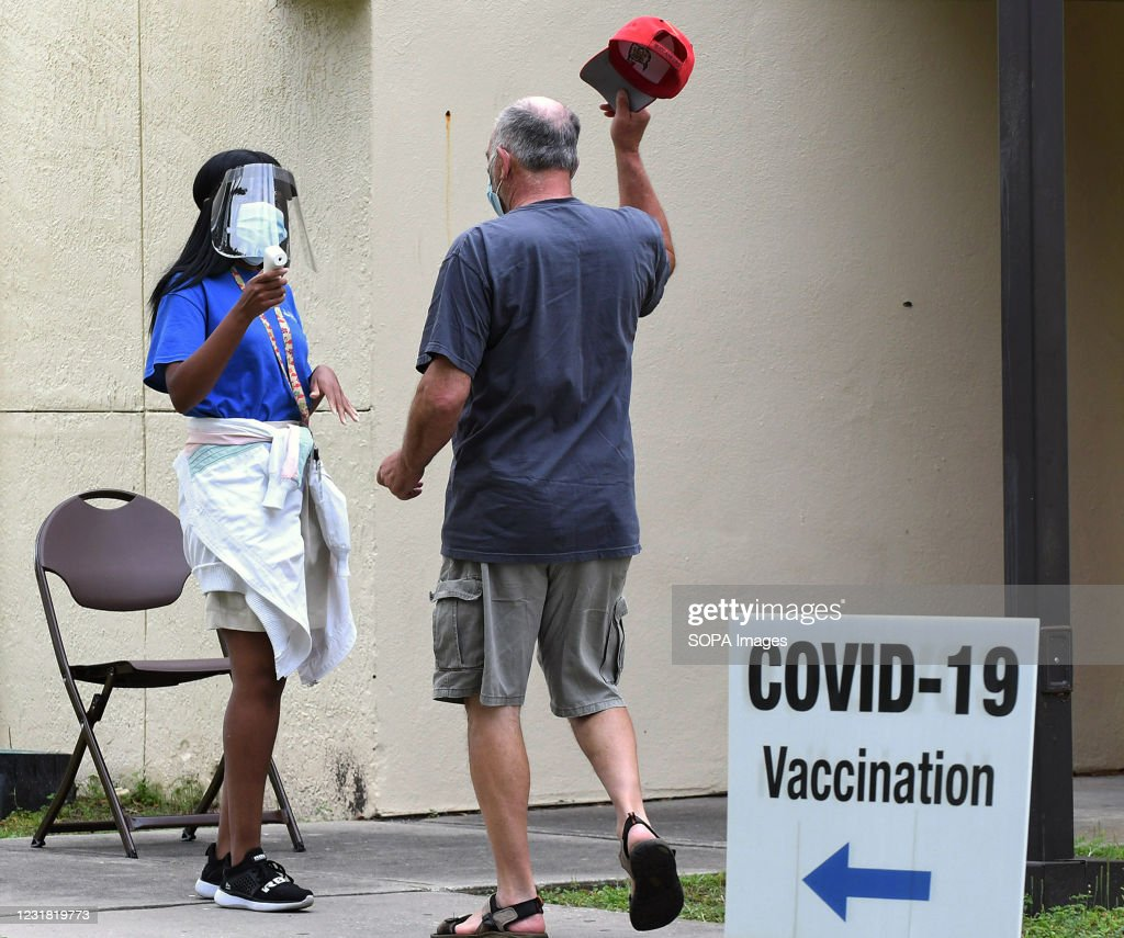 A man removes his hat for a temperature check as he arrives... : News Photo