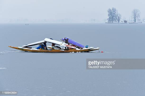 A man removes snow from a boat near a frozen portion of Dal lake after a heavy snowfall in Srinagar on January 16 2020