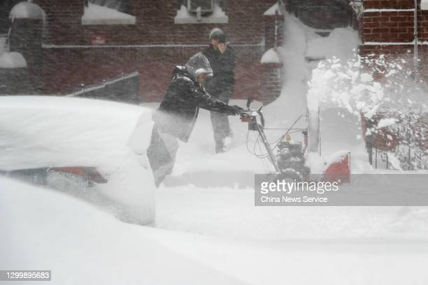 Man removes snow from a street during a snowstorm on February 01, 2021 in the Queens borough of New York City.