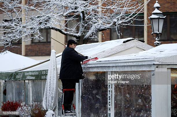 A man removes snow from the roof of a tent at the Viktualienmarkt on December 9 2010 in Munich Germany Meteorologists claim this winter to be...