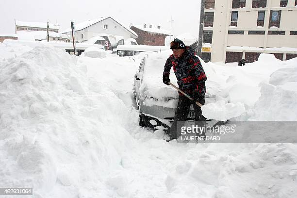 A man removes snow on his car on February 1 2015 after the heavy snowfall of the last two days in the ski resorts of SaintLarySoulan southwestern...