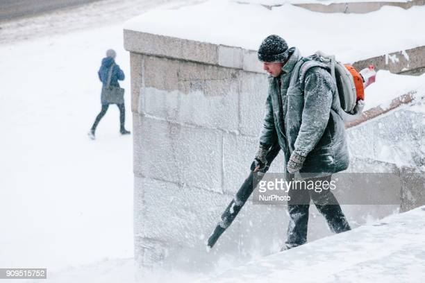 A man removes snow with a blower in Kharkiv Ukraine on 23 January 2018