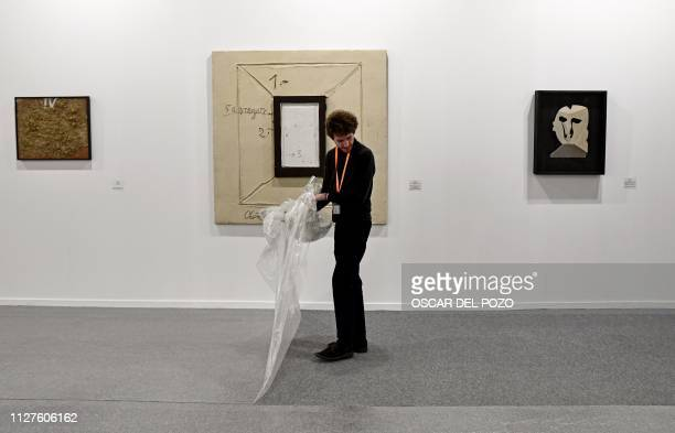 A man removes the plastic covering a carpet as gallery workers prepare artworks to be exhibited at the International Contemporary Art Fair in Madrid...