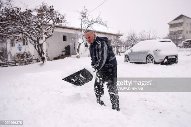 A man removes the snow from his yard during heavy snow fall over Pristina on January 10 2019