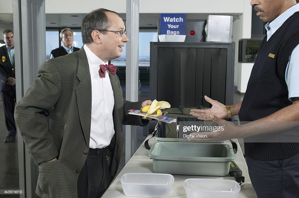 Man Removing a Banana Peel at Airport Customs : Stock Photo