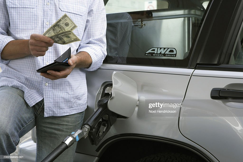 Man removing bank notes from wallet while refuelling car, mid section : Stock Photo