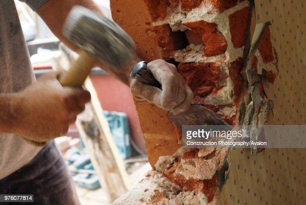 Man removing brick wall of house, UK.