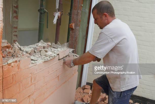 Man removing brick wall of house UK