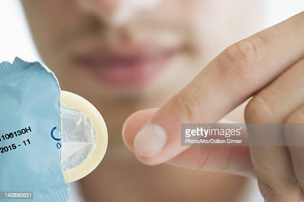 Man removing condom from wrapper, cropped