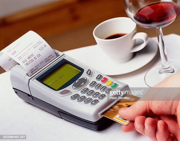 Man removing credit card from chip and pin machine, close-up