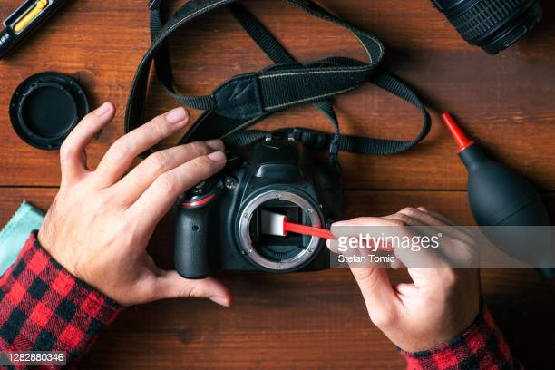 man removing dust from a dslr camera sensor - sensor stock pictures, royalty-free photos & images
