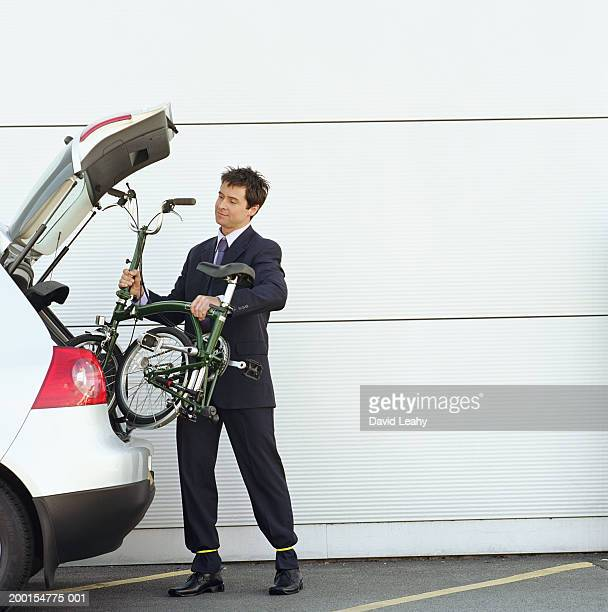 Man removing folding bicycle from boot of car