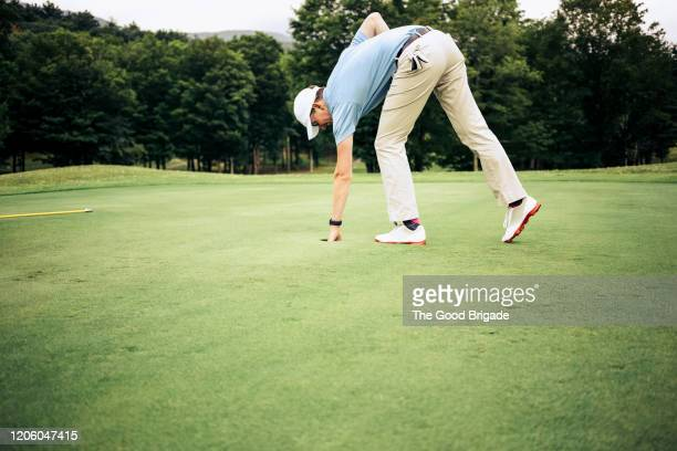 man removing golf ball from cup - putting green stock pictures, royalty-free photos & images