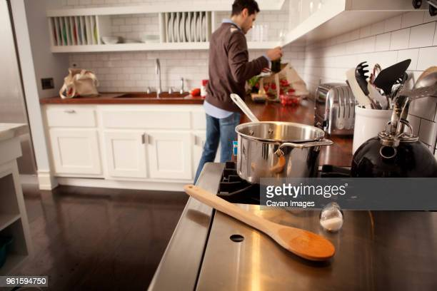 Man removing groceries from shopping bag in kitchen