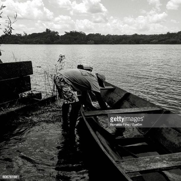 man removing water from boat - filho stock pictures, royalty-free photos & images