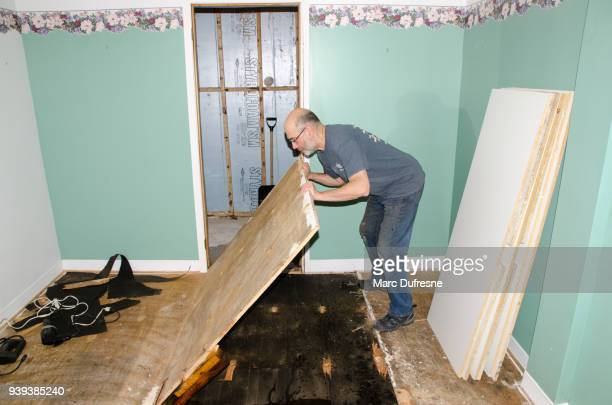 Man removing wooden board from floor after damage in basement caused by sewer backflow due to clogged sanitary drain