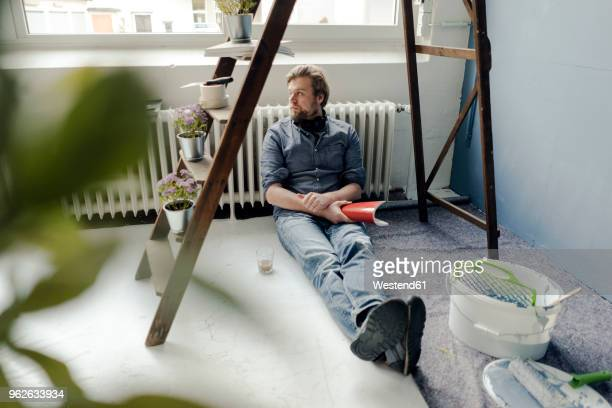 man renovating room sitting on the floor having a rest - renovierung themengebiet stock-fotos und bilder