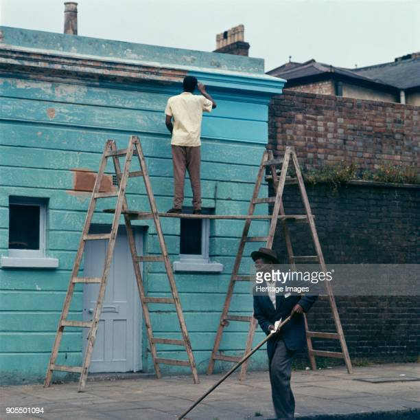 Man repainting the exterior of a business premises in Kentish Town London 1960s Artist John Gay