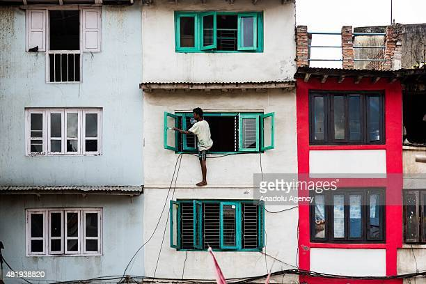 Man repaints a window frame after it was damaged during the earthquakes in Kathmandu on July 25, 2015. Today marks the 3 month anniversary of the...