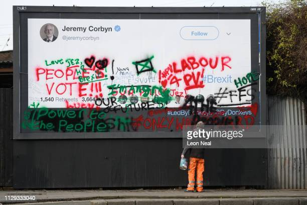 A man repaints the frame around a defaced poster from the proremain group Led By Donkeys featuring a blank tweet by Labour Party leader Jeremy Corbyn...