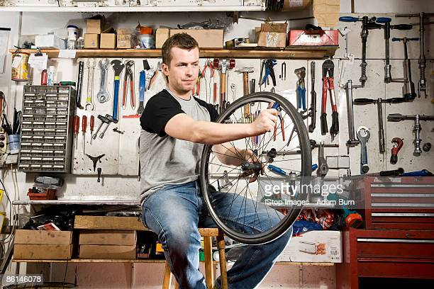 A man repairing a bicycle tire in a workshop