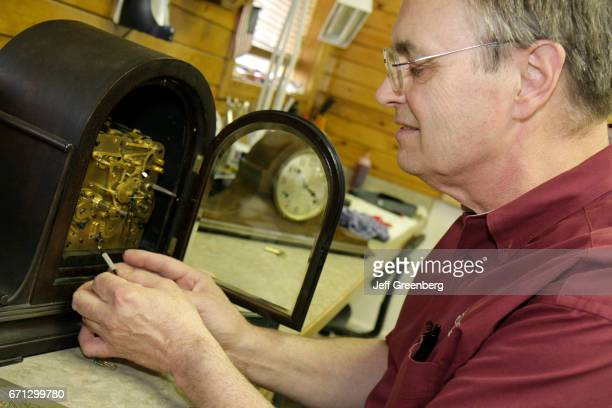 A man repairing a Black Forest cuckoo clock at Frankenmuth Clock Company