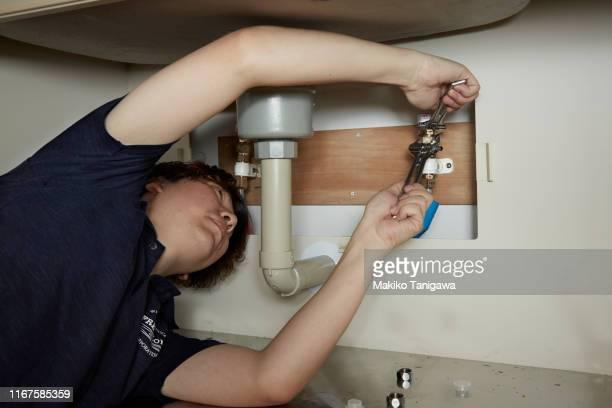 man repairing a kitchen sink - makiko tanigawa ストックフォトと画像