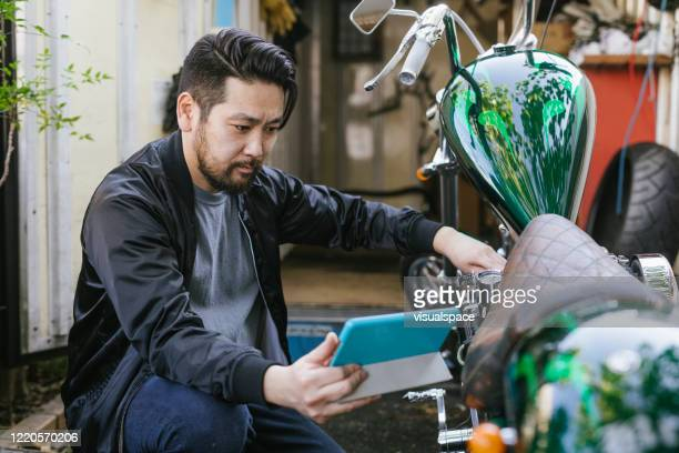 man repairing a motorcycle with the help of online videos - adult videos japan stock pictures, royalty-free photos & images