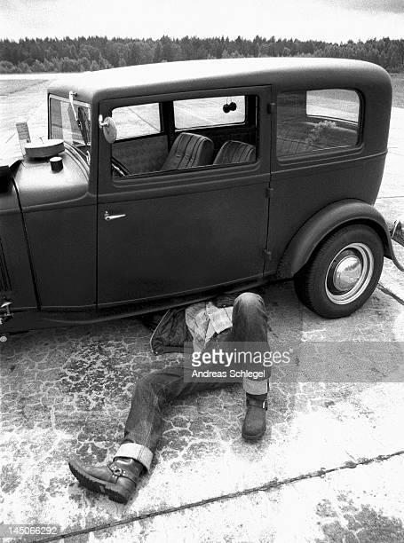 A man repairing an old car