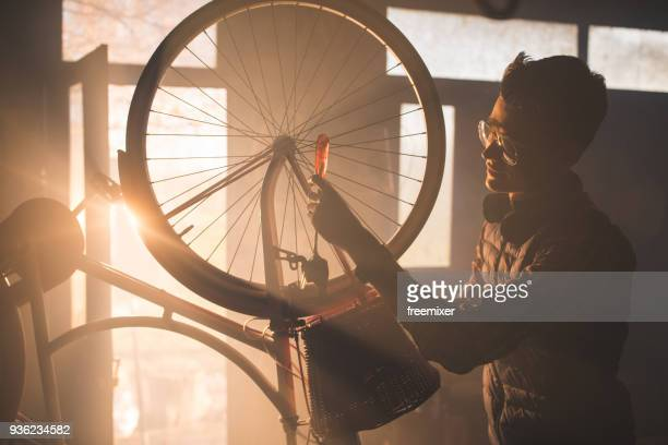 man repairing bicycle in workshop - bicycle shop stock pictures, royalty-free photos & images