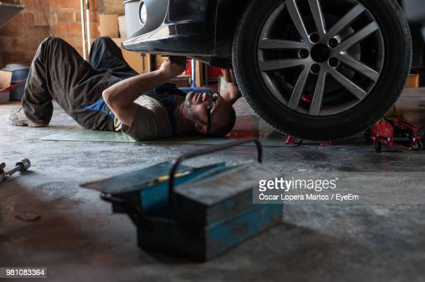 man repairing car in garage - garage stock pictures, royalty-free photos & images