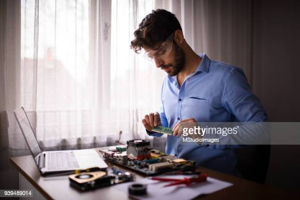 Man repairing computer at home.