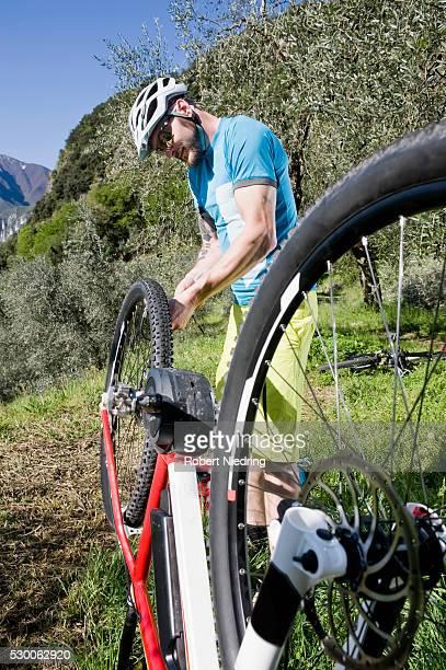 man repairing flat type on electic-mountainbike - posizione descrittiva foto e immagini stock