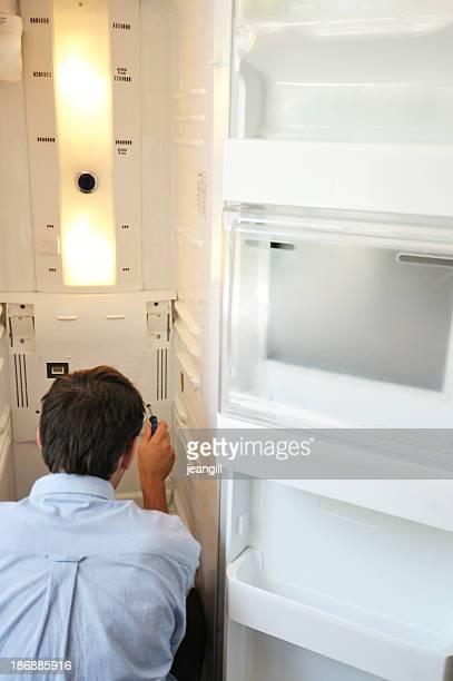 man repairing fridge