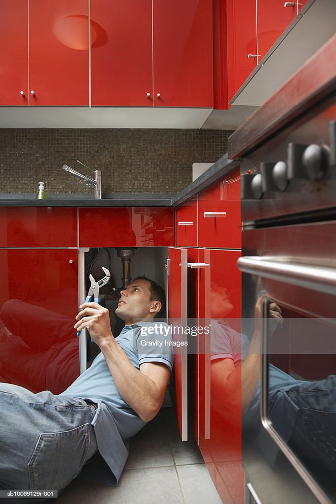 Man repairing kitchen sink, side view : Stockfoto