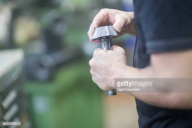 man repairing machinery part - sigrid gombert foto e immagini stock
